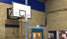 Wall mounted gymnasium basketball goals.